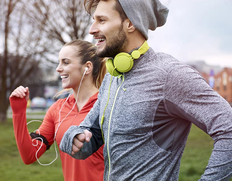 Technically, headphones are those huge things that you wear right over your head. Those would be way too bulky and hot for most runners. No wonder the male runner has taken the headphones off his ears!